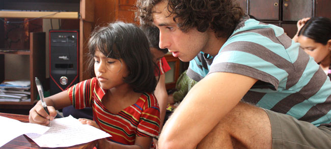 volunteers helping orphanage children with homework