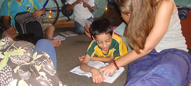 volunteer helping an orphan with assignment